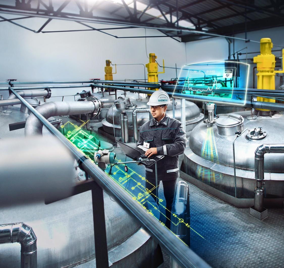 Mann in Arbeitskleidung überprüft an einem Tablet-PC Messwerte einer Anlage der chemischen Industrie. Die digitalen Daten werden visualisiert durch digital Layer.