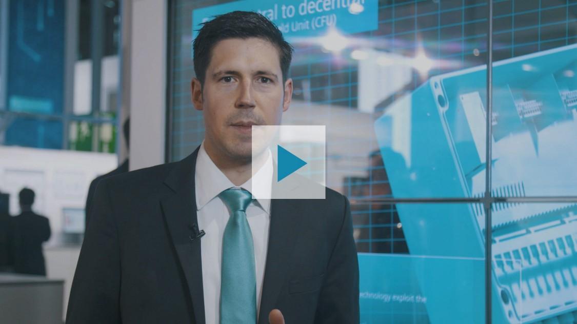 La foto muestra a Manuel Keldenich. Como experto de Siemens en tecnología de control de procesos, presenta el sistema de control de procesos SIMATIC PCS 7 V9.0 en un podcast que comienza cuando se pulsa el botón de reproducción.