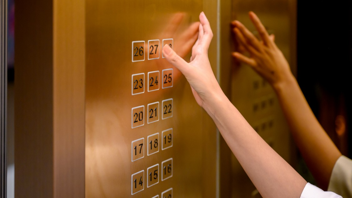 Femme poussant un bouton dans un ascenseur.
