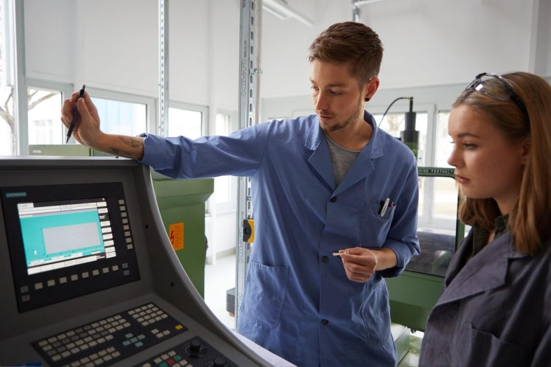 Ein junger Mann und eine junge Frau stehen vor dem Eingabefeld einer Industriemaschine