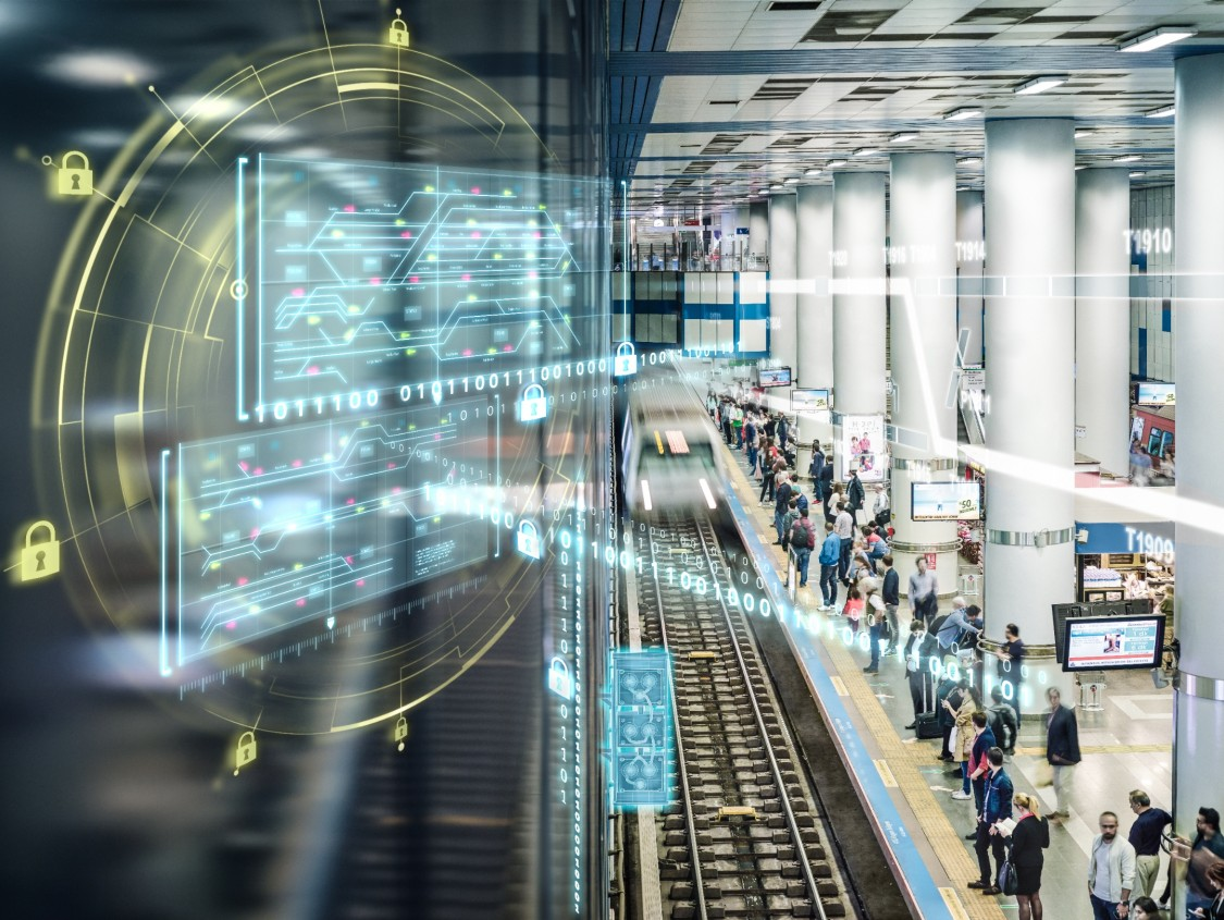 A busy train station platform with digital graphic elements such as cybersecurity icons and binary code demonstrates the digitalization of mobility and related cybersecurity challenges