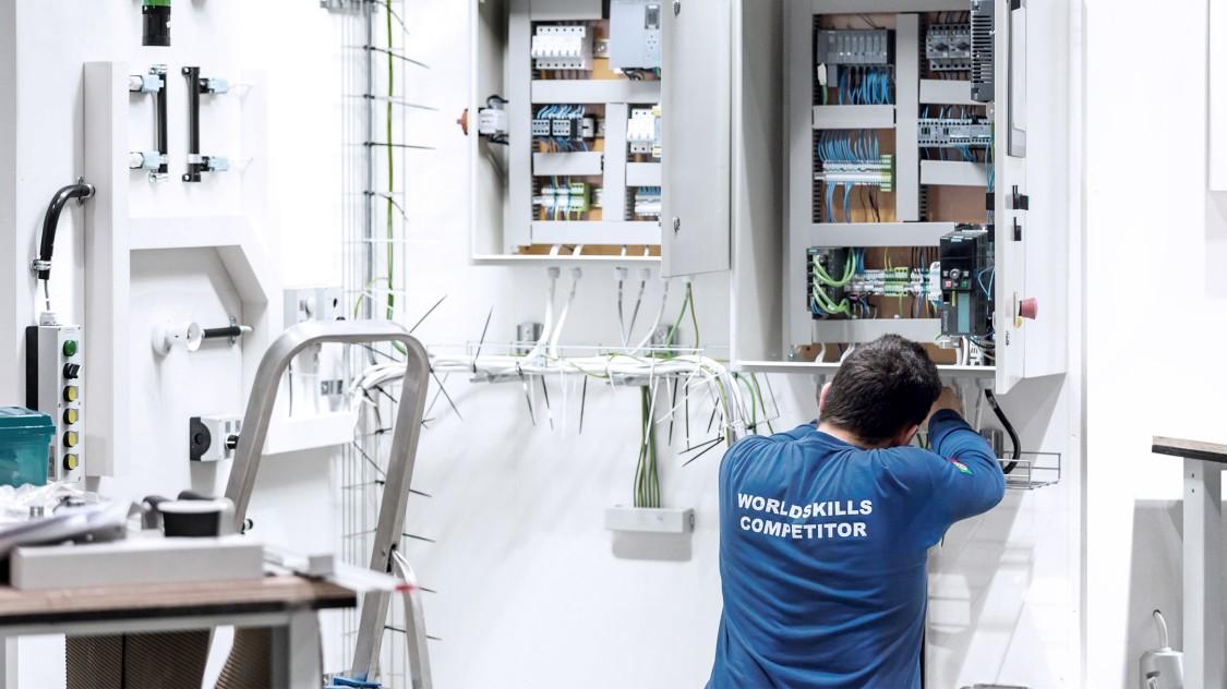 WorldSkills Teilnehmer von Industrial Control installiert Siemens Komponenten in einem Schaltkasten