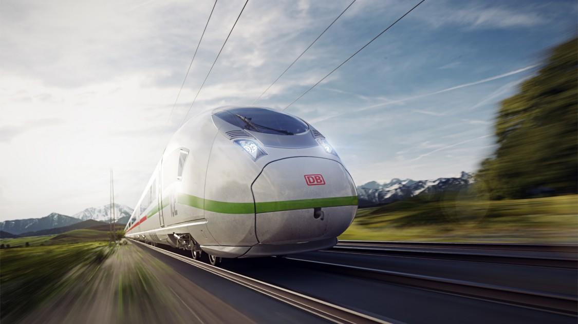 Bild des Velaro MS von Siemens Mobility in leichter Diagonalansicht bei der Fahrt durch eine grüne Landschaft; im Hintergrund sind Berge zu erkenne.