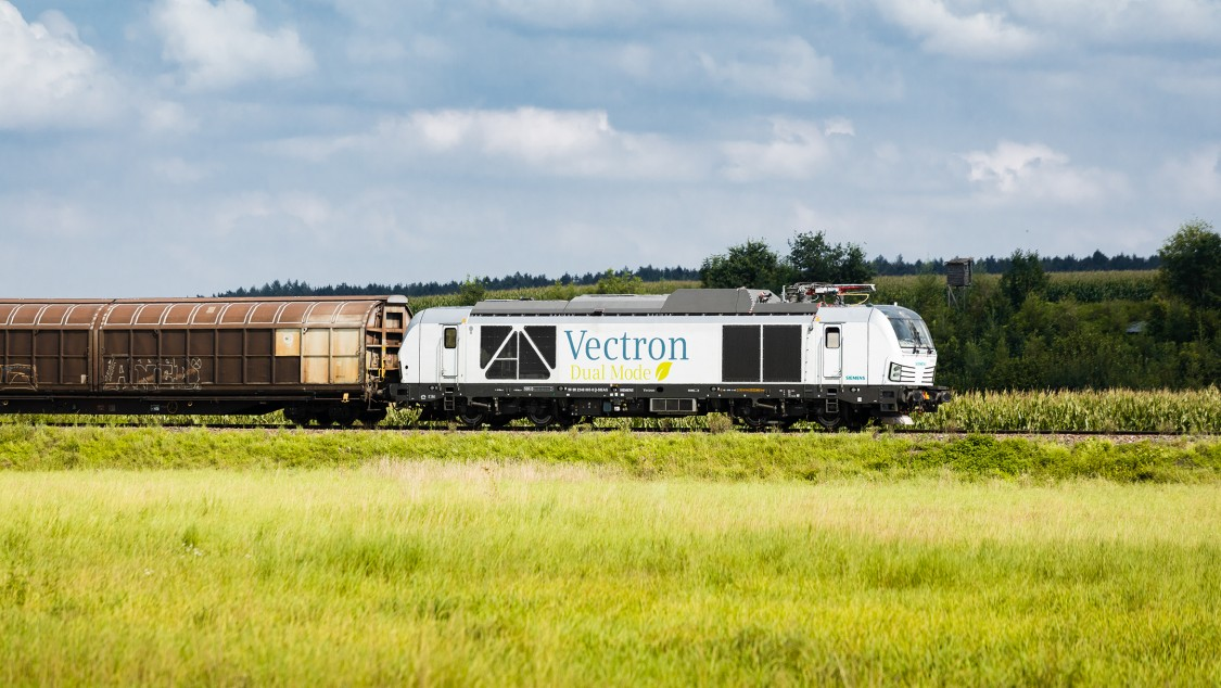 Picture of a Vectron Dual Mode in diesel operation with attached freight cars through a landscape.