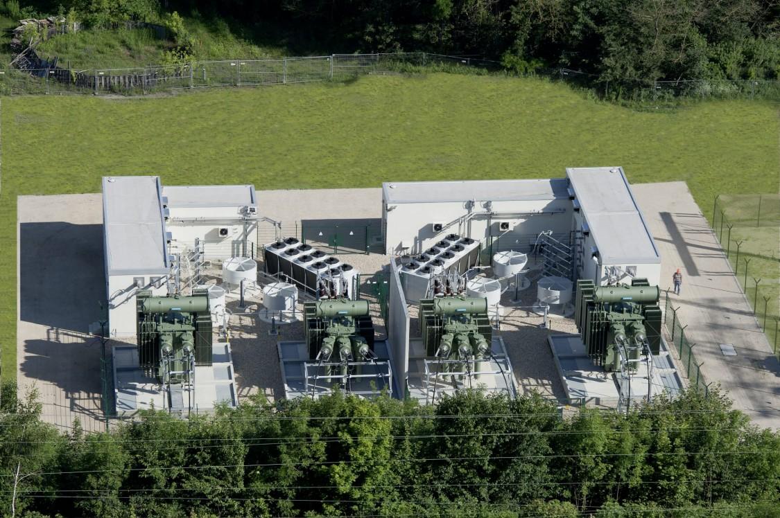 Beispiel eines statischen Frequenzumrichters, wie er in Regensdorf bei Zürich durch Siemens 2021 bis 2023 realisiert wird. Zu sehen sind die Gebäude für die Steuerung und Umrichtermodule, sowie die 50 und 16,7 Hz Trafos, die jeweils drei Drosseln und die Kühleinrichtungen.
