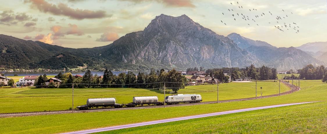 Image of a Vectron Dual Mode locomotive running in electric mode with freight cars attached, passing an idyllic mountain landscape.