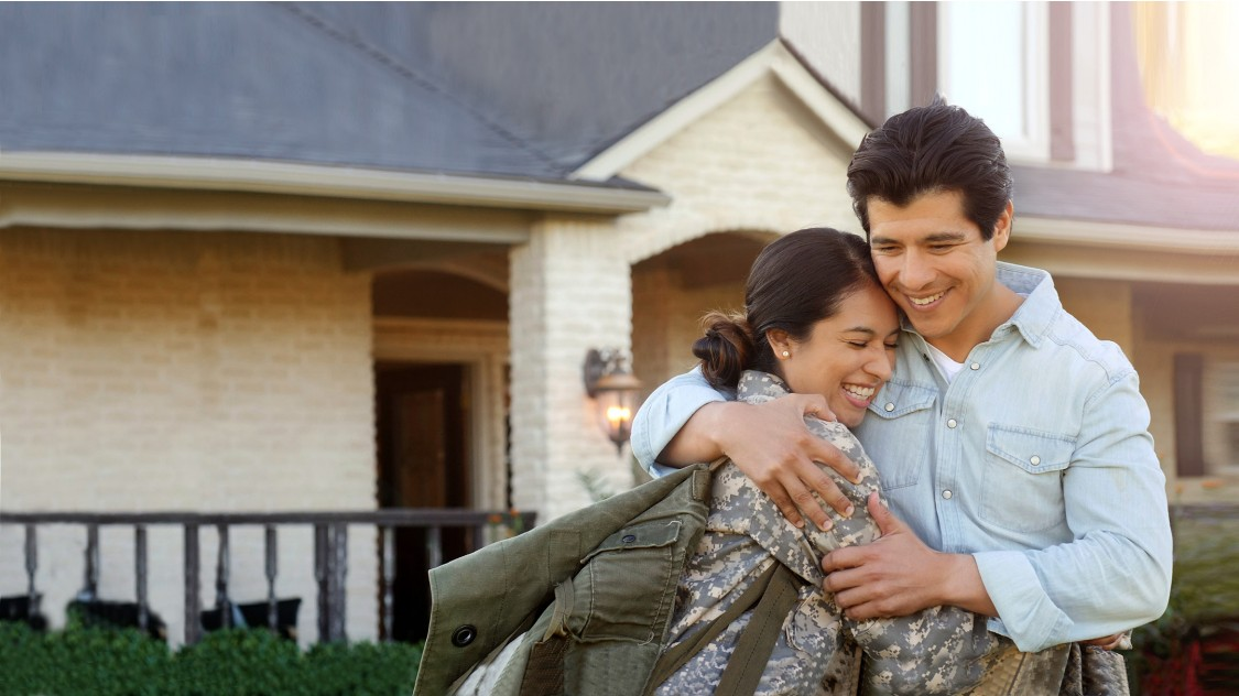 US Veterans woman in uniform returning home hugging family in front of house