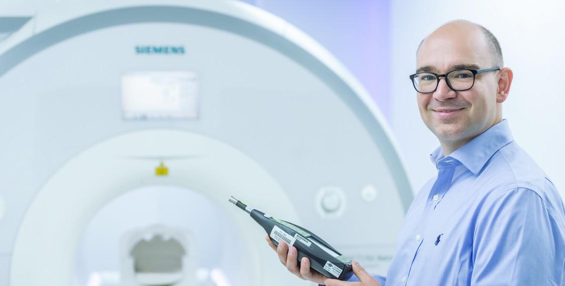 David Grotzki mit Schallmesgerät vor einem MRT