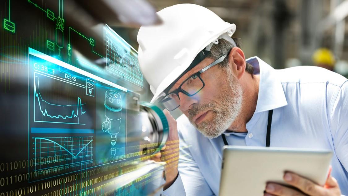 Mitarbeiter mit Sicherheitshelm und Tablet-PC in der Hand nimmt Messwerte auf. Ein Digital Layer zeigt verschiedene Grafiken, die symbolisch für Messwerte in der Anlage stehen.