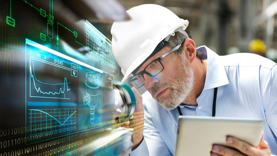 Mitarbeiter mit Sicherheitshelm auf dem Kopf und Tablet-PC in der Hand nimmt Messwerte auf. Ein Digital Layer zeigt verschiedene Grafiken, die für Messwerte in der Anlage stehen.