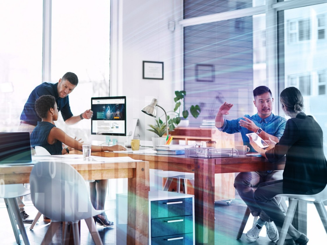 Group of employees in office meeting looking at computer monitor