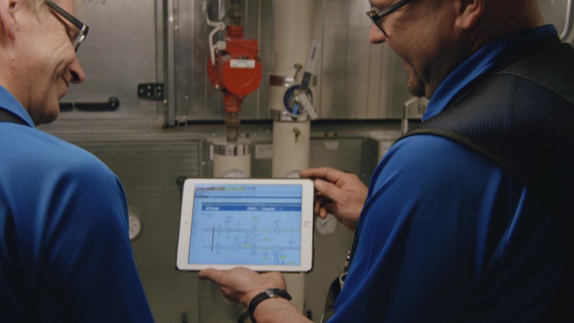 Zwei Wartungsarbeiter im Dienst: gemeinsam schauen sie auf ein Tablet mit Desigo CC.