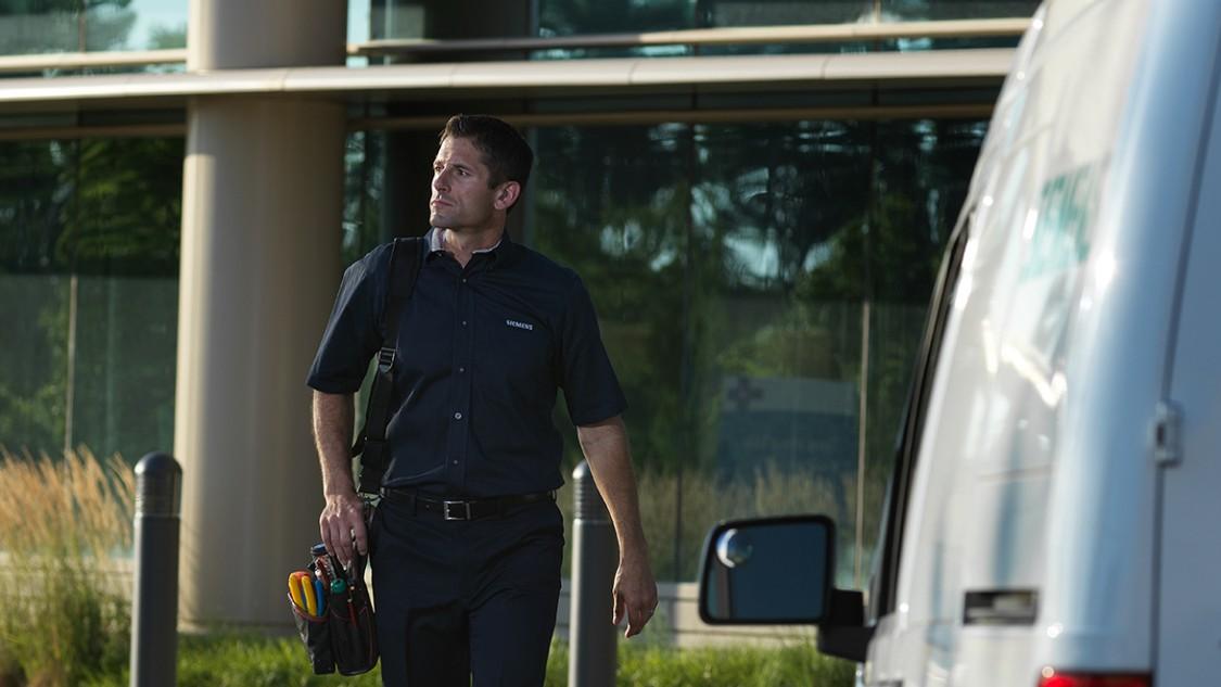 Siemens Fire & Life Safety associate walking toward a Siemens vehicle