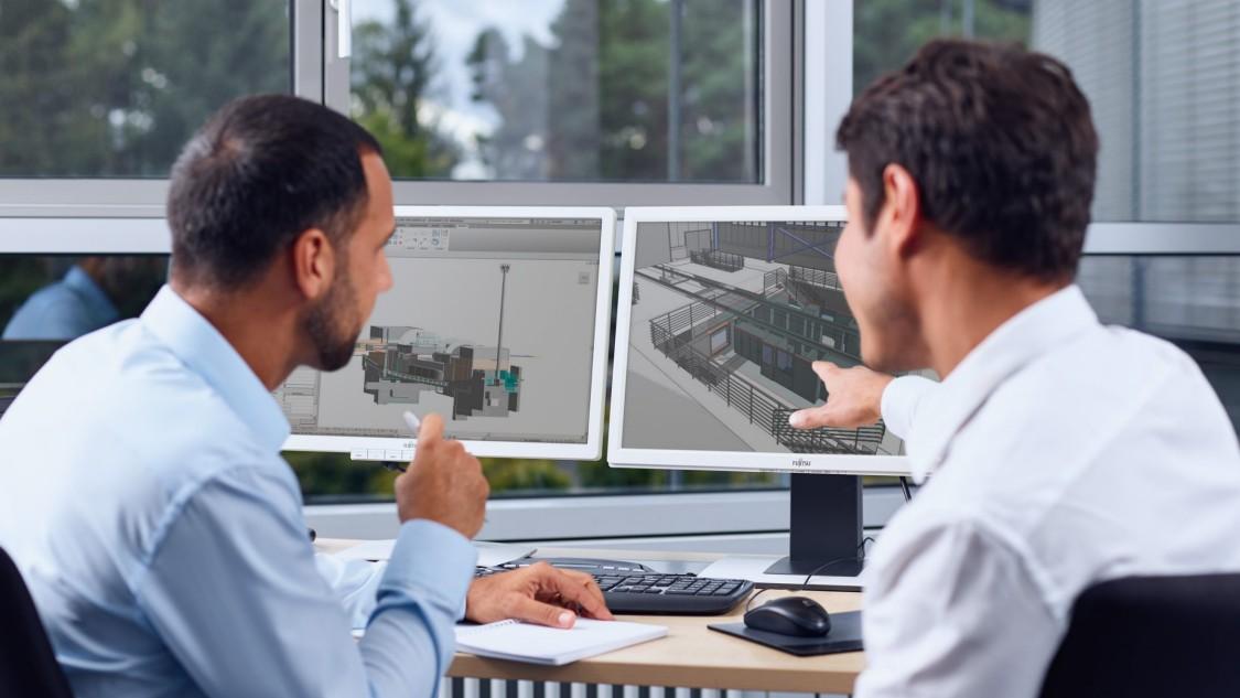Zwei Experten prüfen ein 3D-Modell eines Bahnprojekts