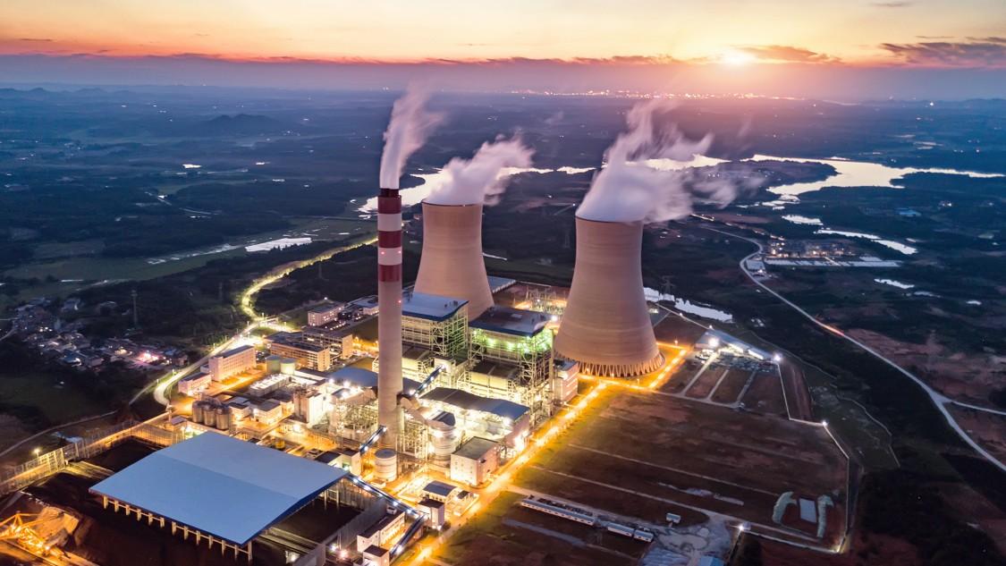 Ein Wärmekraftwerk bei Nacht mit symbolisierten Kommunikationsverbindungen