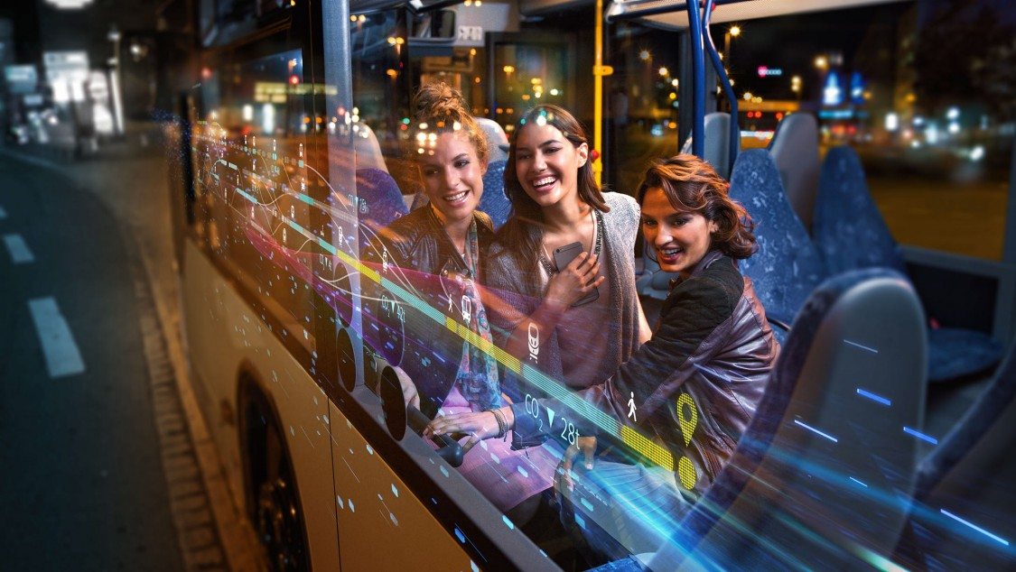 Three fresh-faced young women sit on a bus at night, the scene is overlaid with digital graphic elements representing seamless mobility