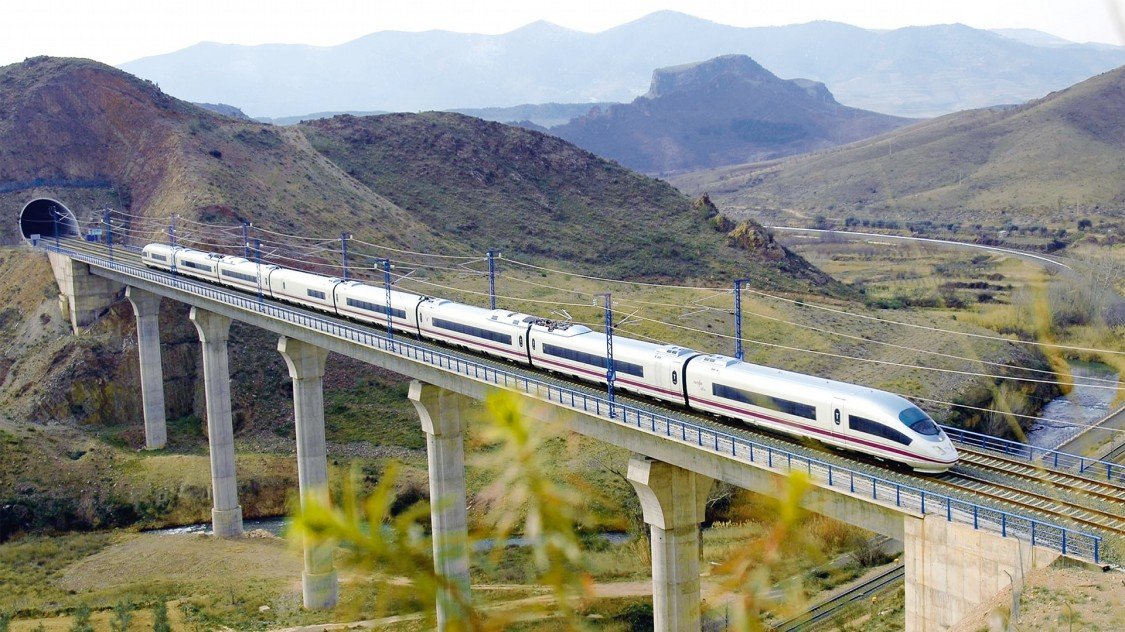 Picture of the Velaro E from Siemens Mobility in diagonal view driving over a bridge in the middle of a Spanish hilly landscape.