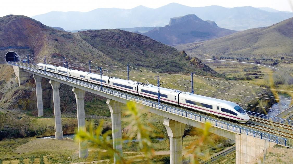 Bild des Velaro E von Siemens Mobility in Diagonalansicht bei der Fahrt über eine Brücke inmitten einer spanischen Hügellandschaft.