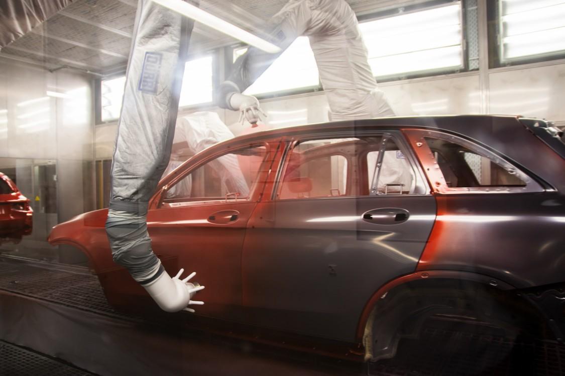 Långa robotarmar sprayar en bil