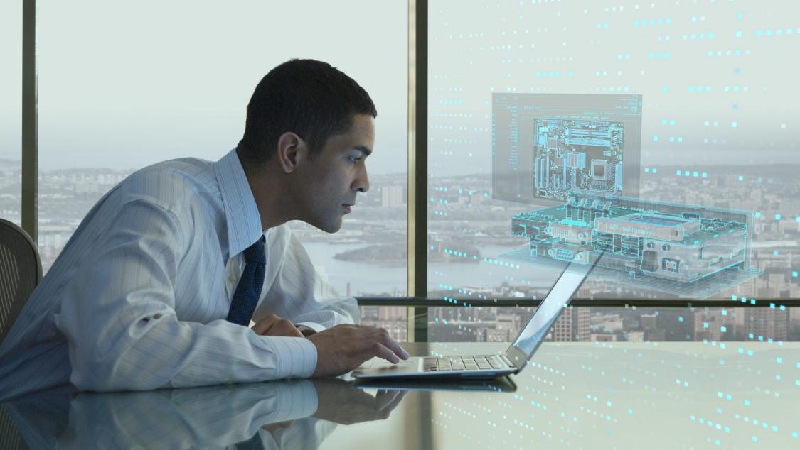 Lehrkraft sitzt an seinem Laptop und benutzt eine Siemens Software, die als Hologramm dargestellt ist