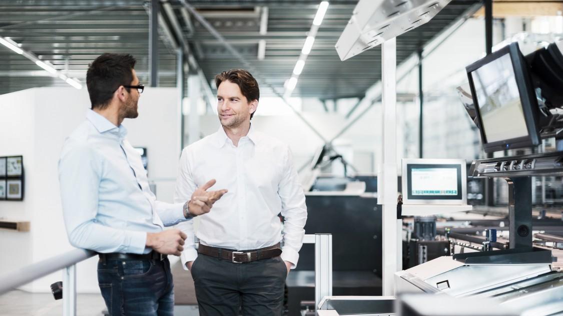 Zwei Systemingenieure unterhalten sich vor einem Kontrollpult mit mehreren Monitorbildschirmen