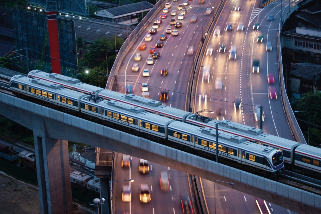 A metro train in Bangkok with smooth traffic flowing in the background demonstrates the benefits of fast, efficient rail travel for cities
