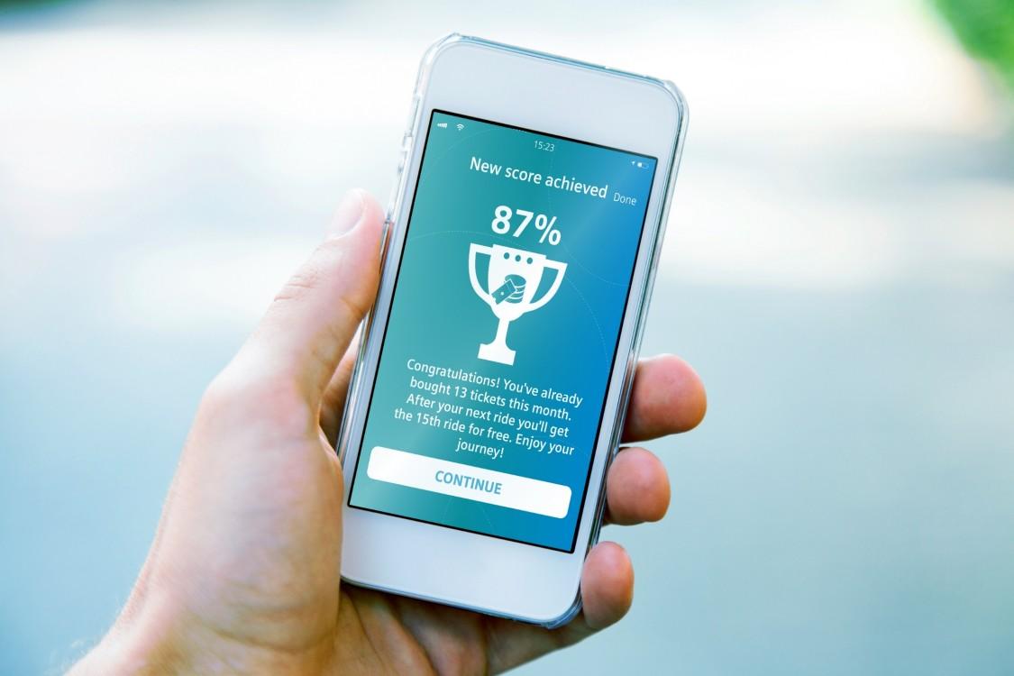 Hand mit Smartphone, auf dessen Display eine Trophäe mit 87 %-Status abgebildet ist.