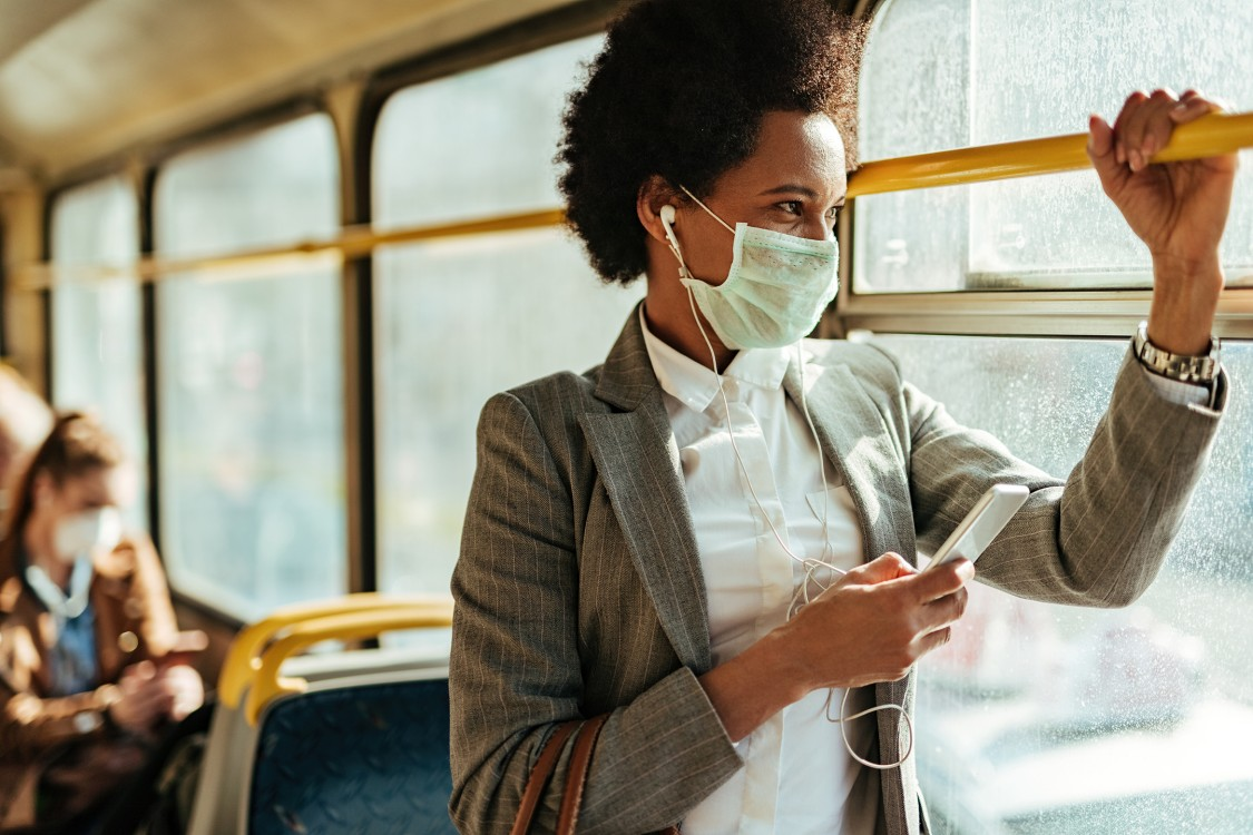 Photo of a women taking public transit with a mask on