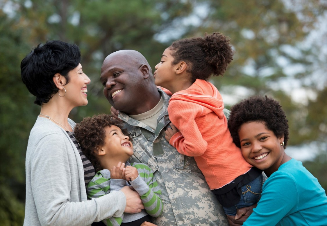 US Military soldier in uniform getting hugged by family