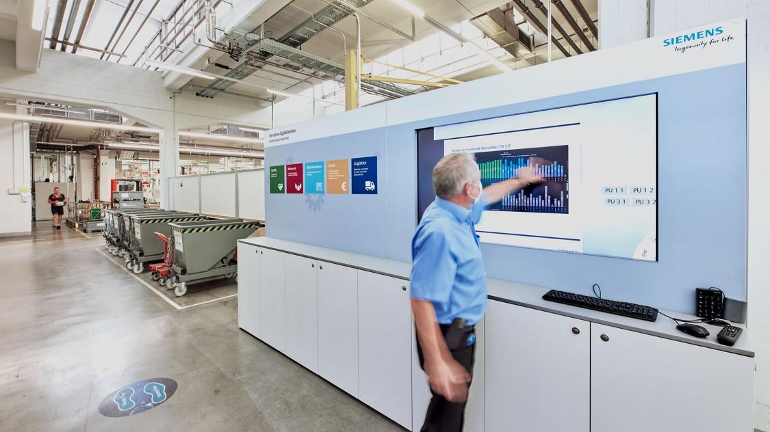Das Bild zeigt die hochmoderne Fertigungshalle der Siemens Elektromotorenfertigung in Bad Neustadt. Im Vordergrund steht ein Mitarbeiter an einem großen Touchscreen.