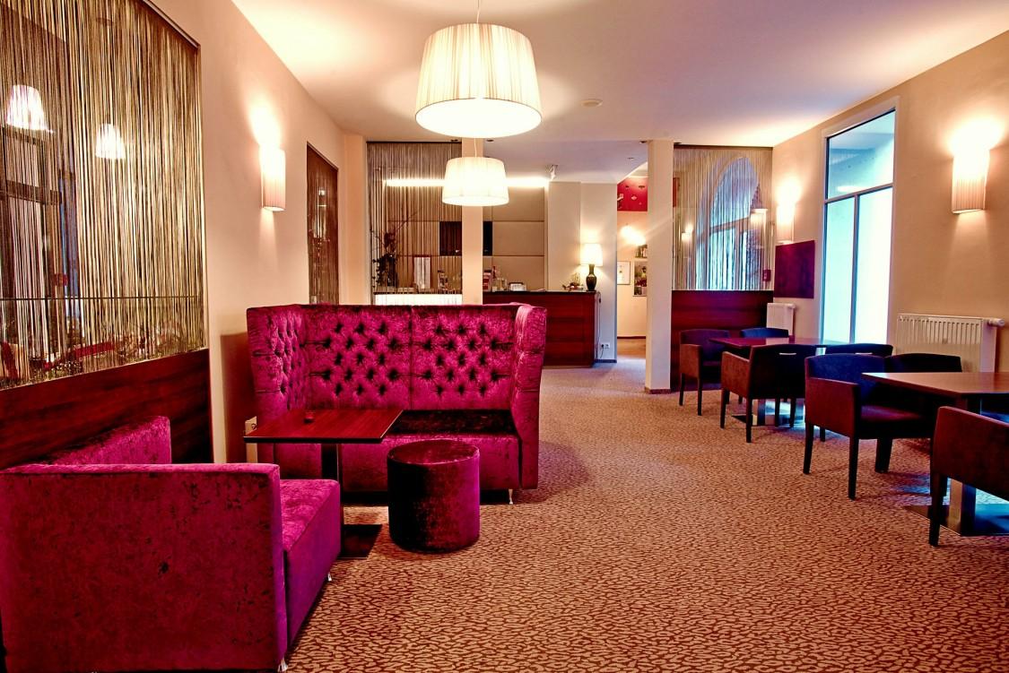 salão social do hotel sustentável em viena com sofás bordô, mesas e cadeiras de madeira e a recepção ao fundo