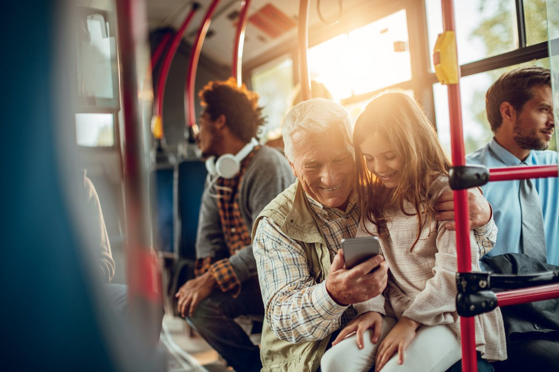 Grandfather and granddaughter sitting in a bus with a smartphone