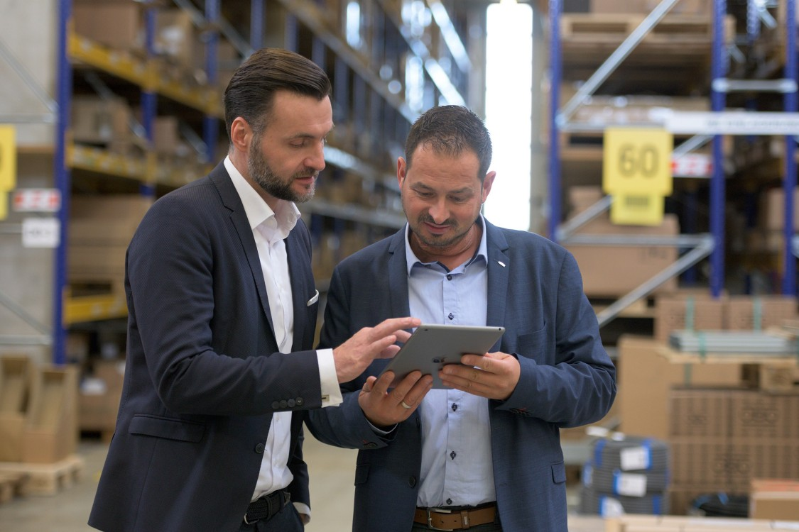 Ricardo Radowski, Director Business Development, Rexel Germany, and Roland Wagner, Siemens, in the REXEL Germany logistics center with tablet
