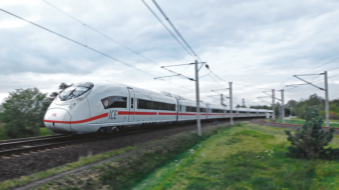 Picture of the Velaro D from Siemens Mobility in diagonal view driving through a green landscape.