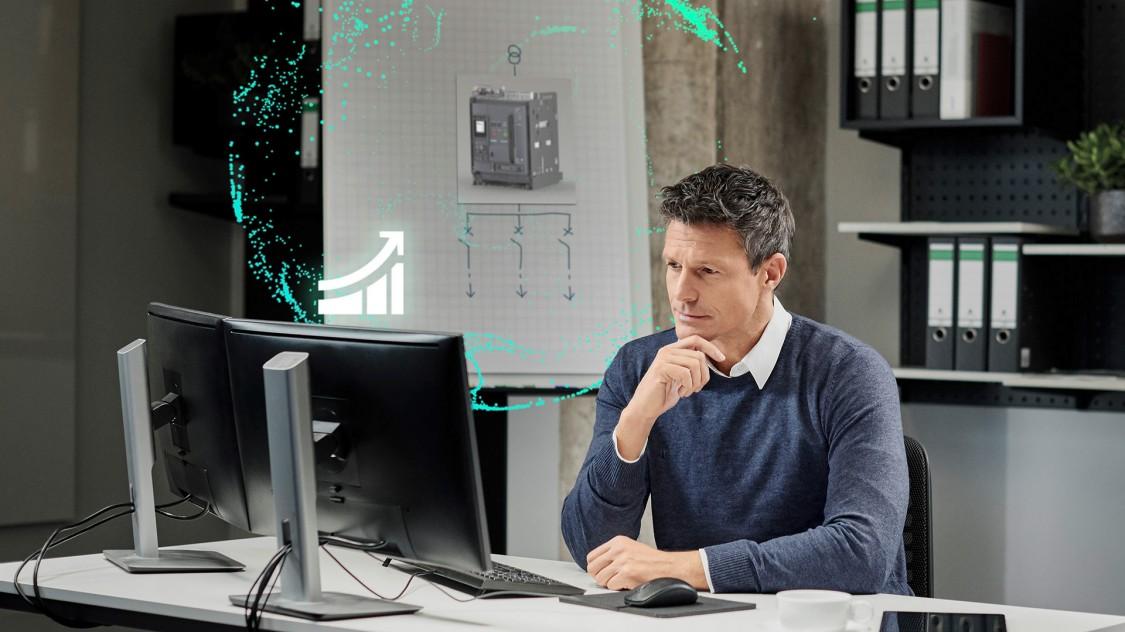 Ein Mann sieht auf einen Monitor, der einen stilisiert-digitalen offenen Leistungsschalter 3WA und Symbole für die Digitalisierung aussendet