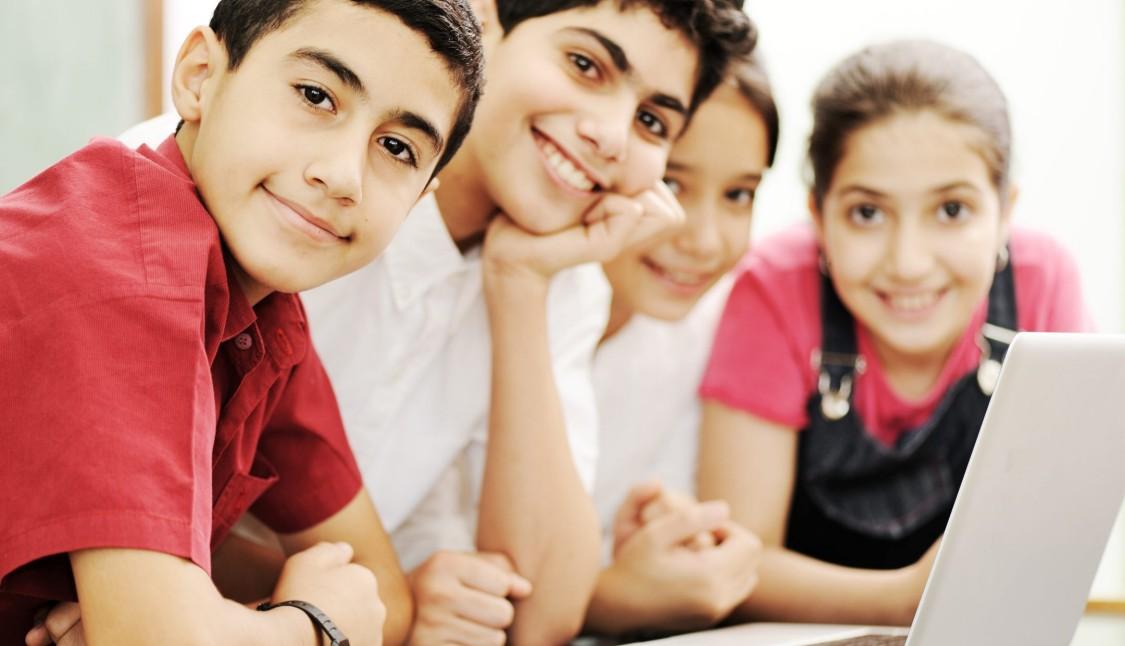 Iraqi kids at a laptop, smiling