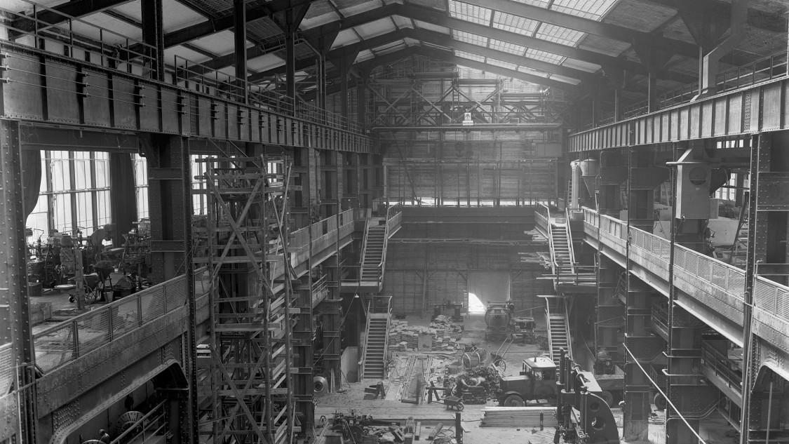 Da der Erweiterungsbau über zwei Galerien verfügt, gliedert sich die komplett unterkellerte Halle in ein Hauptschiff und zwei Seitenschiffe. Letztere sind bereits mit Maschinen zur mechanischen Teilebearbeitung ausgestattet, als die Bauarbeiten im Erdgeschoss noch andauern.