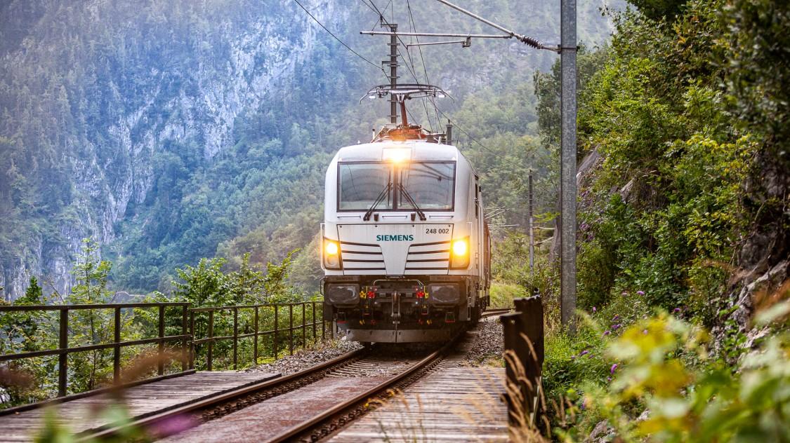 Der Vectron Dual Mode im elektrischen Betrieb in Frontalsicht auf dem Gleis in grüner Landschaft.