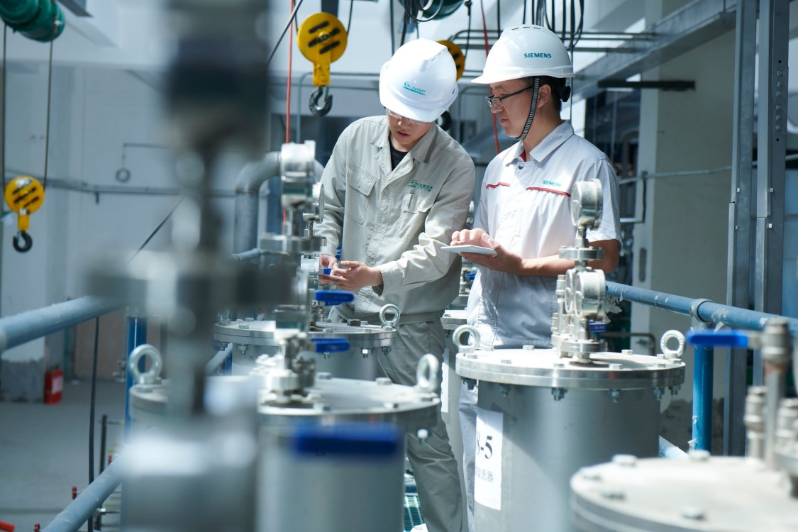 Two worker in workwear review a biotechnological production process at the Cathay Industrial Biotech Ltd. plant. in Chinese Wusu.