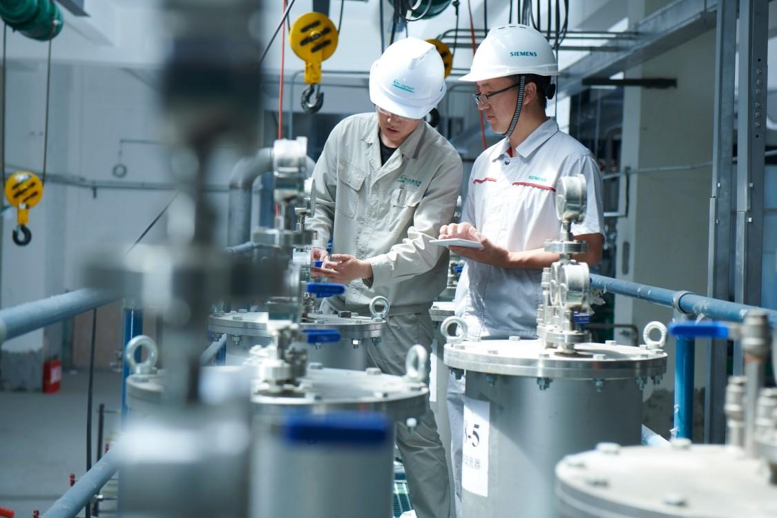 Zwei Männer in Arbeitskleidung überprüfen einen Prozess der biotechnologischen Produktion in der Anlage von Cathay Industrial Biotech Ltd. im chinesischen Wusu.