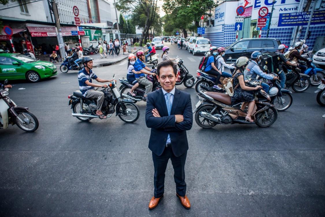 Foto de homem de braços cruzados e motos passando ao fundo