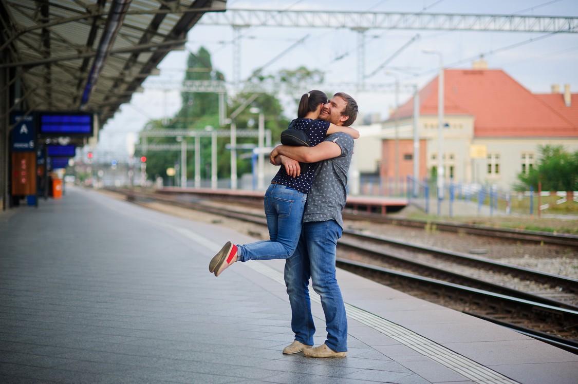 Couple on a train platform hugging