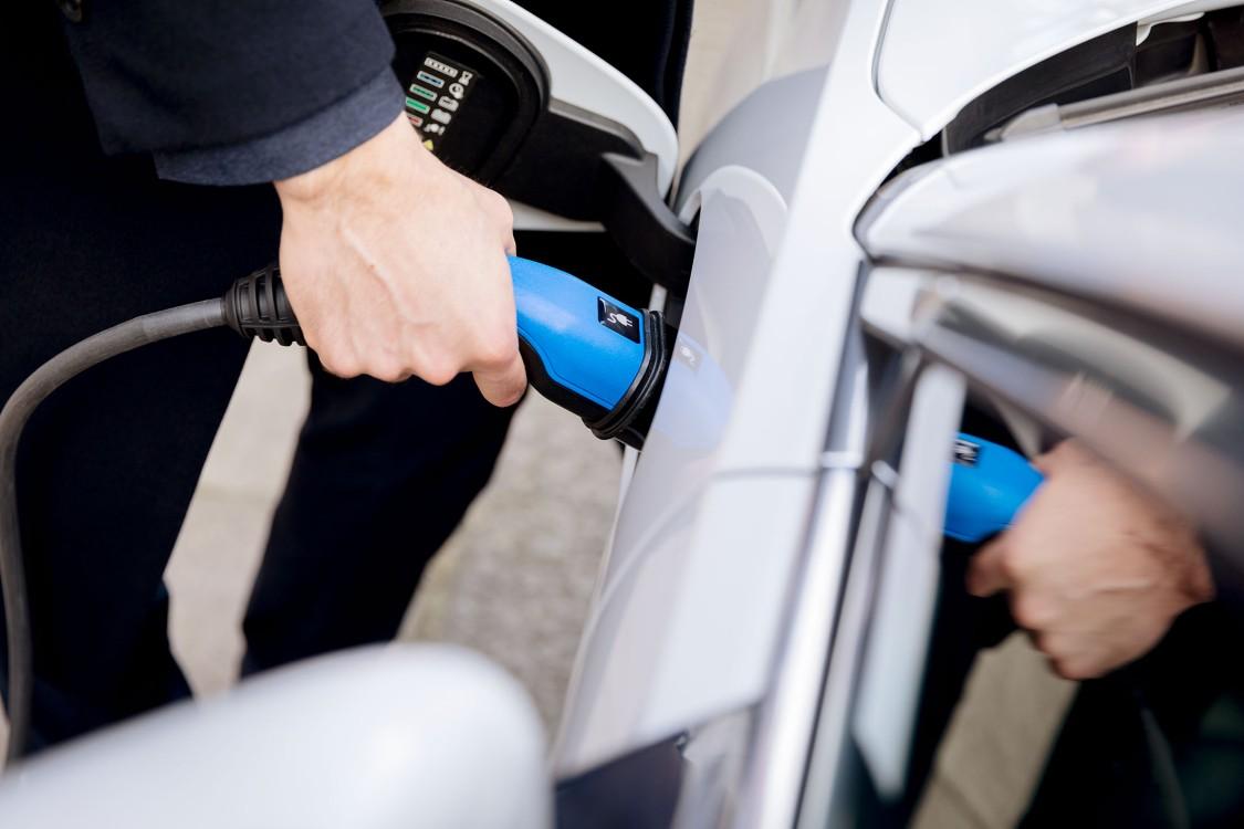man charging electric vehicle at EV Charging station