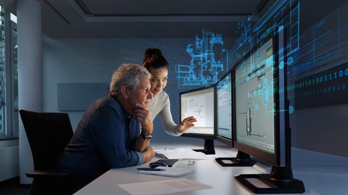In einer Leitwarte: Seitlich aufgenommener Mann am Schreibtisch vor drei Monitoren sitzend. Neben ihm steht eine Frau, die auf einen der Bildschirme zeigt.