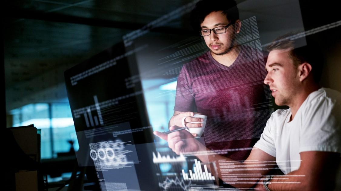 dois jovens rapazes, um ocidental e outro asiático analisando dados e uma tela de computador