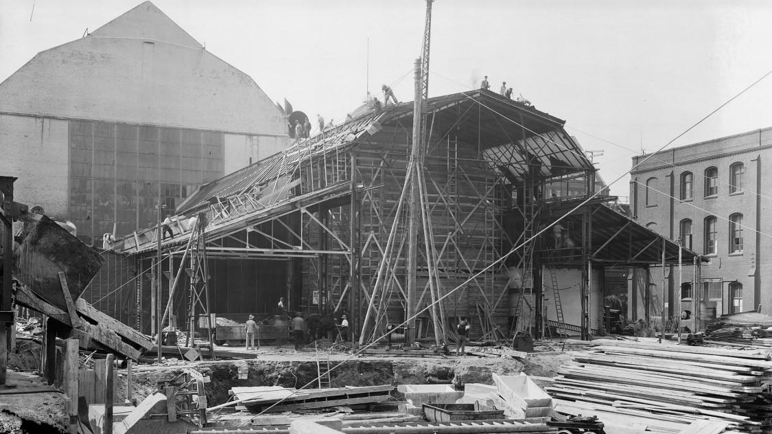 Eröffnet werden die Bauarbeiten im Sommer 1939 mit dem Abriss mehrerer Gebäude, die sich nördlich der Montagehalle erstrecken. Zu ihnen gehört ein Backsteinbau, der spätestens seit 1911 eine erste, wenn auch mehr oder weniger provisorische Verlängerung darstellt. (Foto 1939)