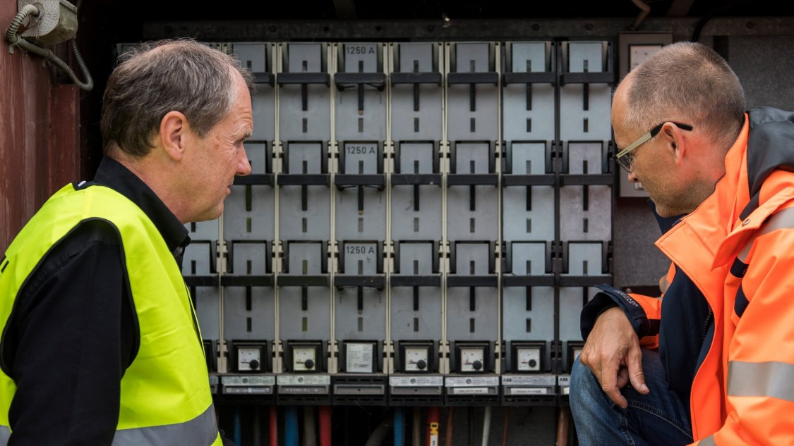Poul Berthelsen and Lars Thierry  in front of a bank of smart meters,  which send millions of valuable data sets  per month to a nationwide data hub.