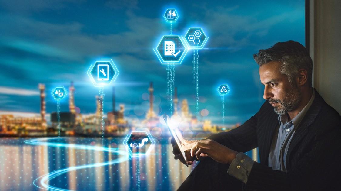 Homem utilizando tablet ao fundo uma grande metrópole com filtros azuis representando as soluções digitais do software para indústria comos