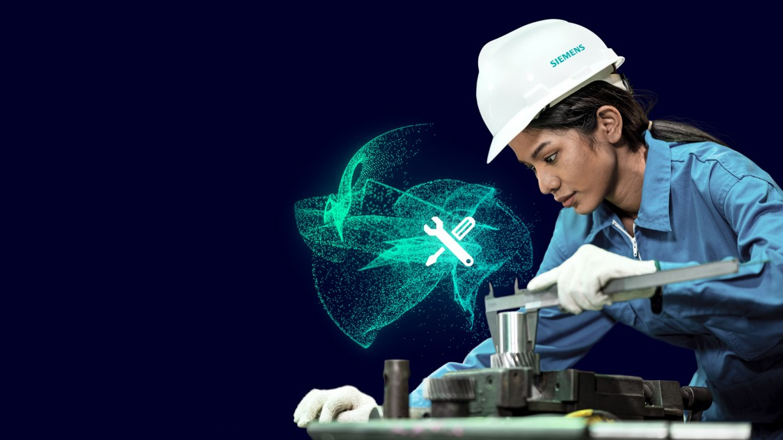 The picture shows a training scene in the Siemens Electric Motor Factory in Bad Neustadt. A young female employee wearing safety goggles is bending over a production piece. At her side is a man who is training her. In the background, out of focus, other employees.