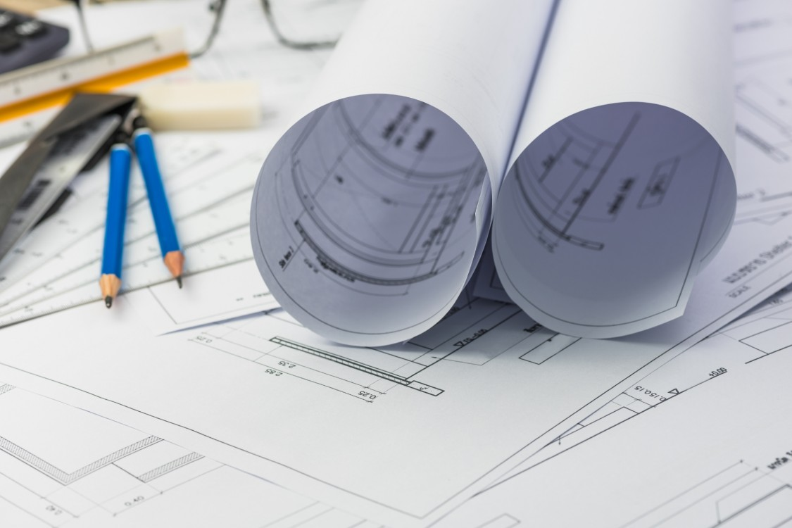 Contact Siemens today. This image shows blueprints and pencils.